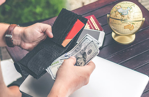 Person holding wallet with cash